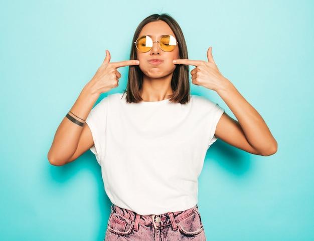 Mujer hermosa joven mirando a cámara. chica de moda en verano casual camiseta blanca y pantalones vaqueros en gafas de sol redondas. la hembra positiva muestra emociones faciales. modelo divertido soplando sus mejillas. Foto gratis