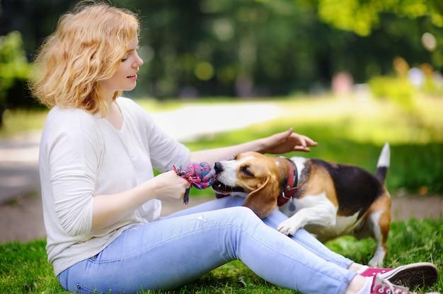 Mujer hermosa joven con el perro del beagle en el parque del verano. amante mujer dueña con su mascota doméstica. Foto Premium