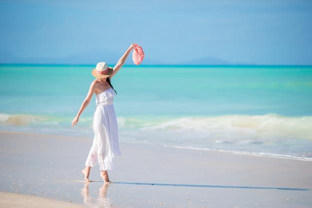 Mujer hermosa joven en la playa tropical de arena blanca. Foto Premium