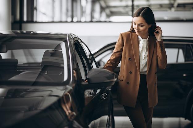 Mujer hermosa joven que elige el coche en una sala de exposición de automóviles Foto gratis