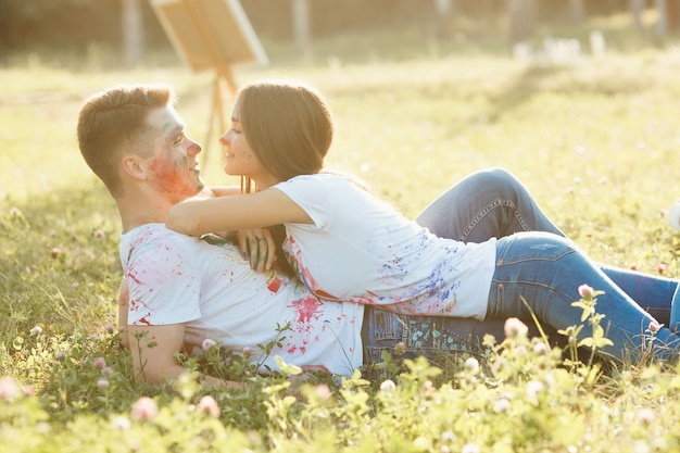 Mujer hermosa joven que pone en su novio que lleva la camiseta coloreada. pareja bastante alegre sonriendo el uno al otro Foto Premium
