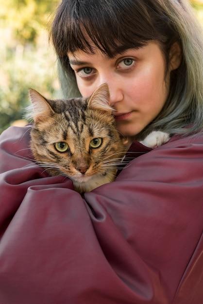 Mujer hermosa joven que sostiene el gato de gato atigrado Foto gratis