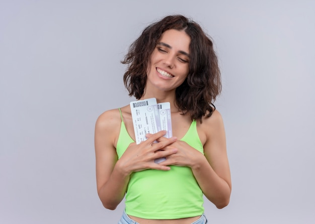 Mujer hermosa joven sonriente que sostiene los billetes de avión en la pared blanca aislada Foto gratis