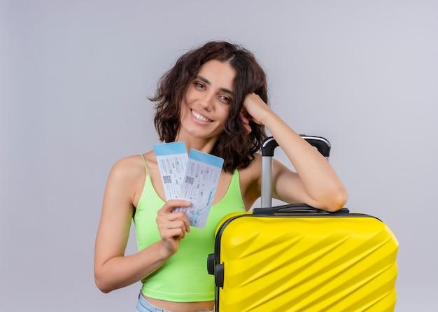 Mujer hermosa joven sonriente del viajero que sostiene los billetes de avión y la maleta en la pared blanca aislada Foto gratis