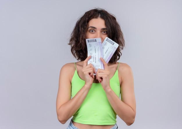 Mujer hermosa joven sorprendida que sostiene los billetes de avión en la pared blanca aislada Foto gratis
