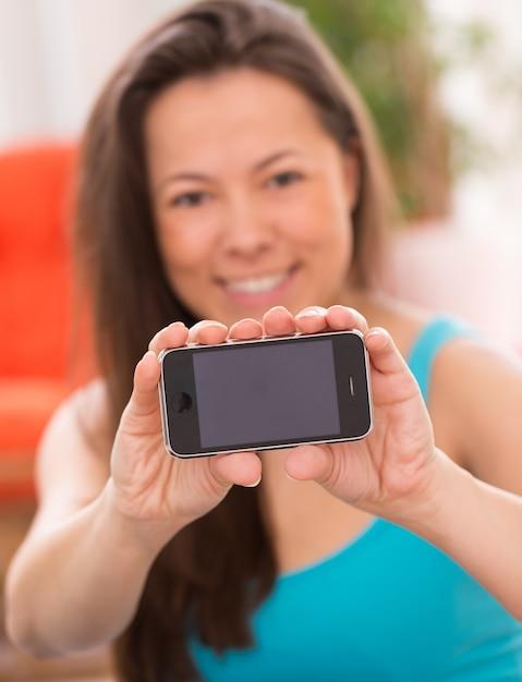 Mujer hermosa joven con teléfono inteligente Foto gratis