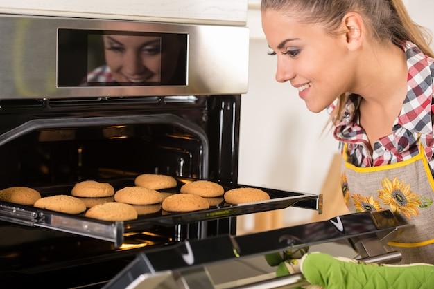 La mujer hermosa joven tira de las galletas del horno. Foto Premium