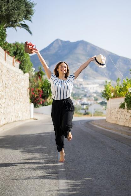 Mujer hermosa joven en vacaciones saltando. en una mano sandalias en el sombrero de segunda mano. Foto gratis