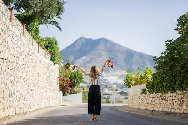 Mujer hermosa joven en vacaciones saltando. en una mano sandalias en el  sombrero de segunda mano.  ef266459688