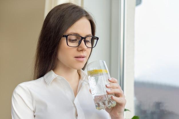 Mujer hermosa joven en vasos con vaso de agua mineral con limón Foto Premium