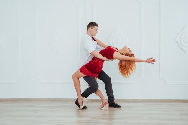 Mujer hermosa joven en un vestido rojo y un baile del hombre aislado en un fondo blanco. Foto Premium