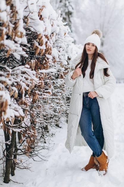 9b067c3f12c1 Una mujer hermosa y de moda con ropa blanca y abrigada caminando en ...