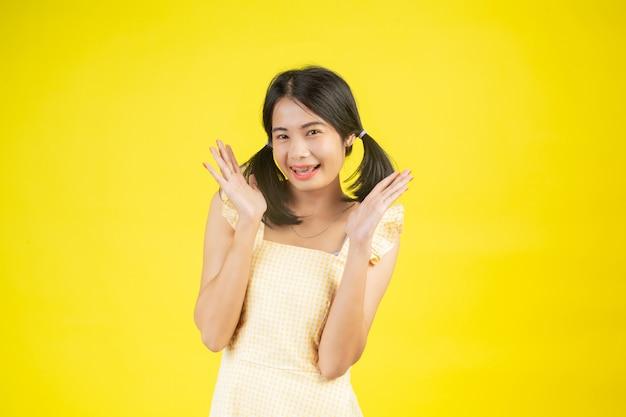 Una mujer hermosa que es feliz mostrando varios gestos en un amarillo. Foto gratis
