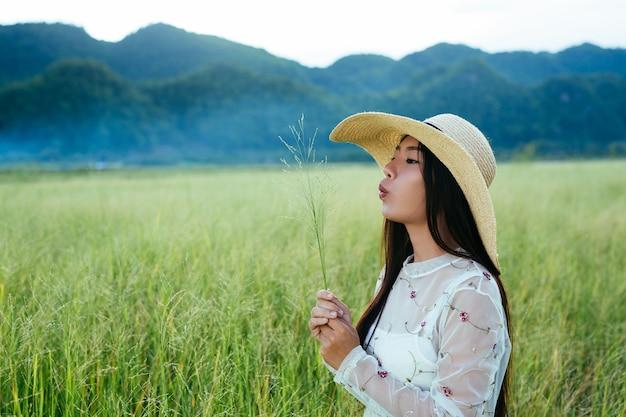 Una mujer hermosa que es feliz en el prado con una gran montaña como a. Foto gratis