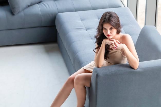 Mujer hermosa que espera y que piensa ideal en sala de estar. Foto Premium