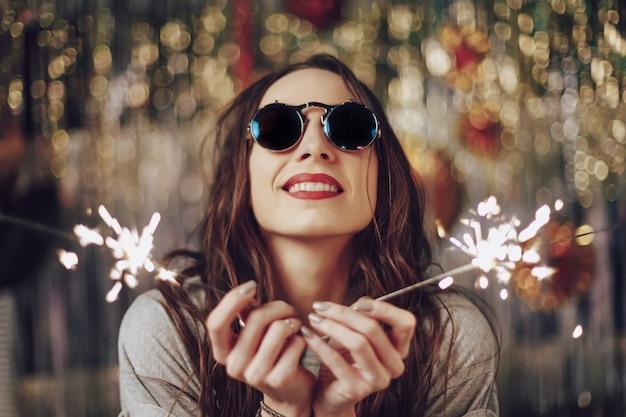 Mujer hermosa que sostiene bengalas en manos Foto gratis