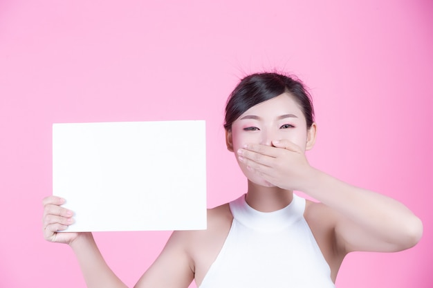 Mujer hermosa que sostiene una hoja del tablero blanco en un fondo rosado. Foto gratis