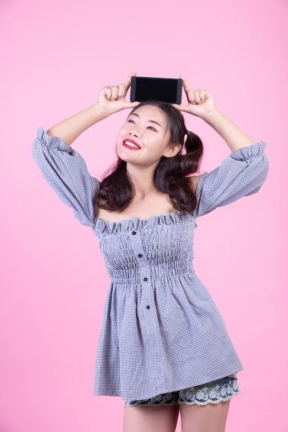 Mujer hermosa que sostiene un smartphone en un fondo rosado. Foto gratis