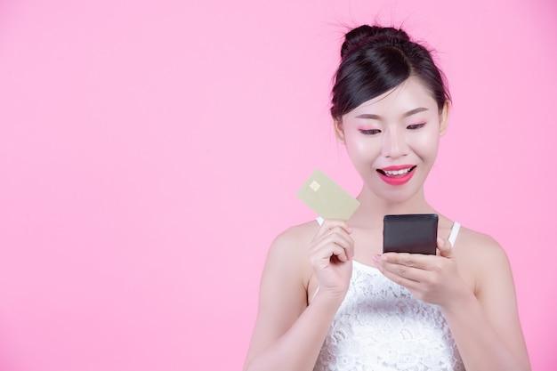 Mujer hermosa que sostiene un smartphone y una tarjeta en un fondo rosado Foto gratis