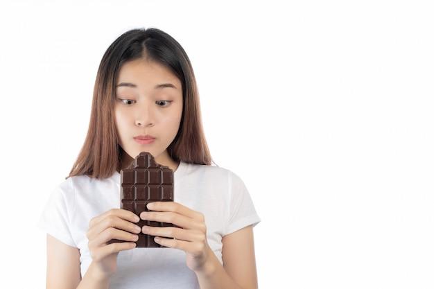 Mujer hermosa con una sonrisa feliz que celebra un chocolate de la mano aislado en un fondo blanco. Foto gratis