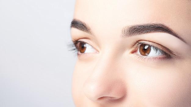 Mujer con hermosas cejas close-up sobre un fondo claro con espacio de copia Foto Premium