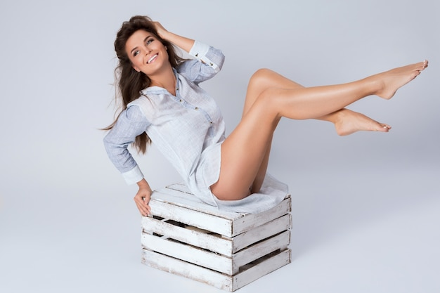 Mujer con hermosas piernas sentado en la caja de madera Foto Premium