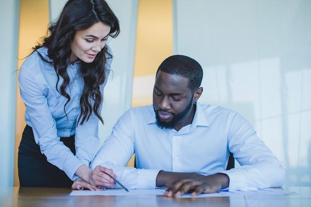 Mujer y hombre de negocios controlando un documento Foto gratis