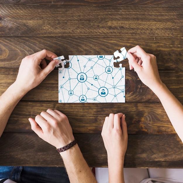 Mujer y hombre resolver rompecabezas de conectividad de red sobre escritorio de madera Foto Premium
