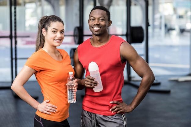 Mujer y hombre sonrientes después de esfuerzo en el gimnasio Foto Premium