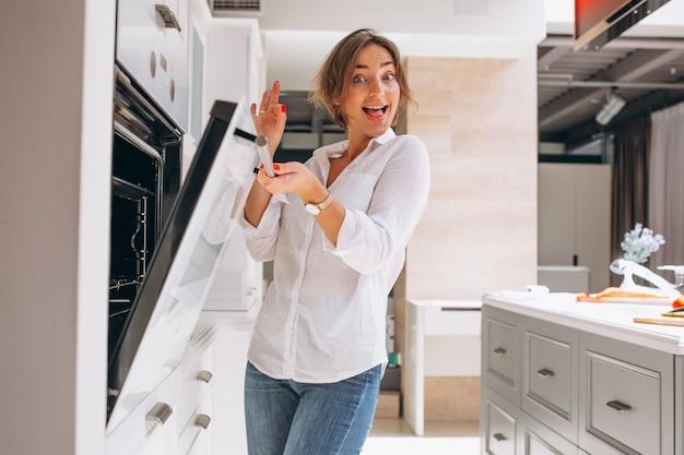 Mujer horneando en la cocina y mirando al horno Foto gratis