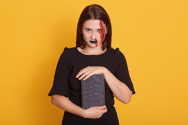 Mujer con horror maquillaje de halloween y herida sangrienta posando en estudio en amarillo, joven mujer con vista peligrosa sostiene libro con encantamiento, vestidos de vestido negro Foto gratis