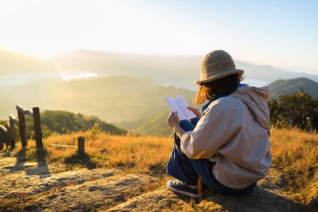 La mujer inconformista lee un libro al hermoso amanecer sobre las montañas. Foto Premium