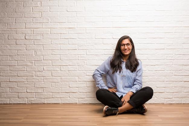 223266cbab8f Mujer india joven sentada contra una pared de ladrillo con las manos en las  caderas, de pie, relajada y sonriente | Descargar Fotos premium