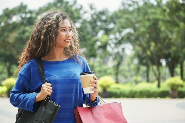 Mujer indonesia caminando en la calle después de ir de compras Foto gratis
