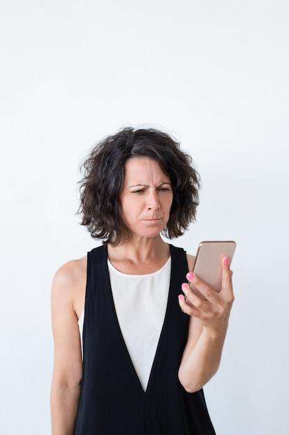 Mujer infeliz estresada con teléfono inteligente recibiendo malas noticias Foto gratis