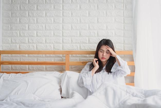Mujer infeliz que se siente enferma después de despertarse en la mañana en la cama Foto Premium