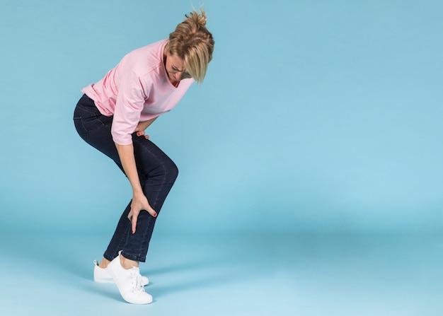 Mujer infeliz que sufre de dolor severo en la pierna. Foto gratis