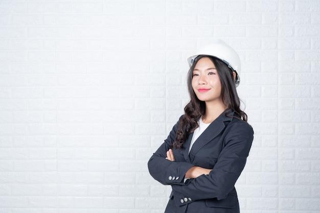 Una mujer de ingeniería que sostiene un sombrero, separa los muros de ladrillos blancos con lenguaje de señas. Foto gratis