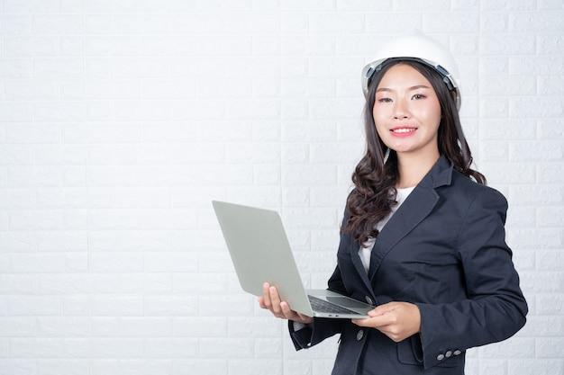 Mujer de ingeniería sosteniendo un cuaderno separado, pared de ladrillo blanco hizo gestos con lenguaje de señas. Foto gratis