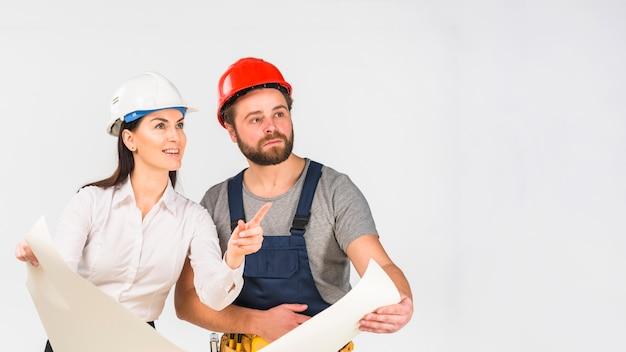 Mujer ingeniero y constructor discutiendo proyecto apuntando lejos Foto gratis