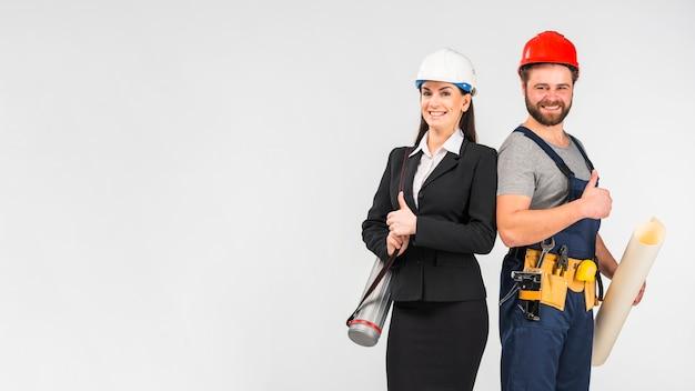 Mujer ingeniero y constructor mostrando los pulgares para arriba Foto gratis