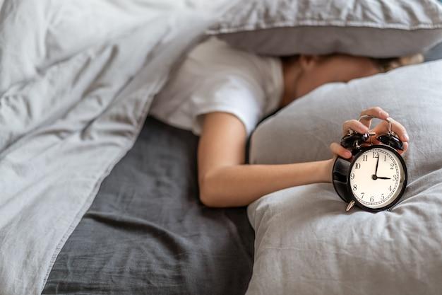 Mujer con insomnio acostada en la cama con la cabeza debajo de la almohada tratando de dormir. insomnio y problemas de sueño. Foto Premium