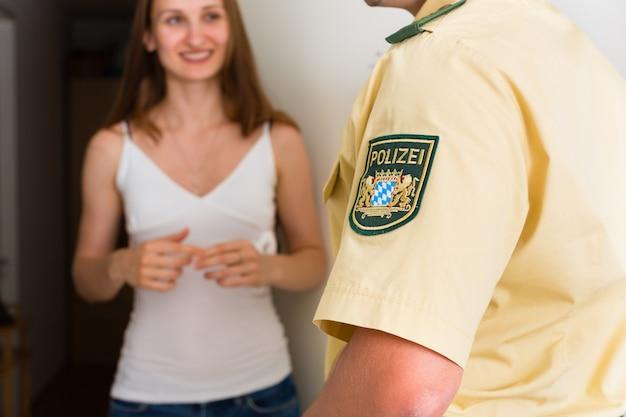 Mujer de interrogación de oficial de policía en la puerta Foto Premium