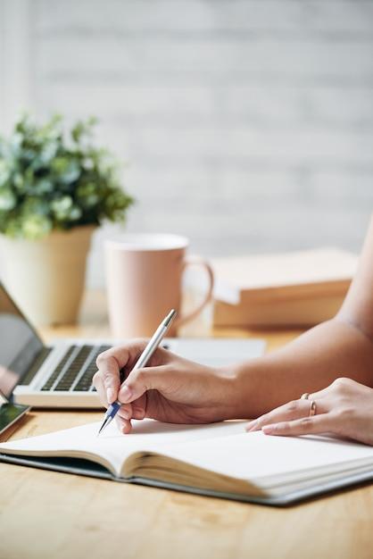 Mujer irreconocible sentada en el escritorio en el interior y escribiendo en planificador Foto gratis