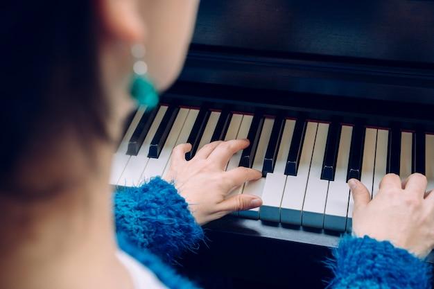Mujer irreconocible tocando el piano. detalle de las manos femeninas que tocan un teclado en casa. profesor pianista músico ensayando música clásica. músico profesional estilos de vida en interiores. Foto Premium