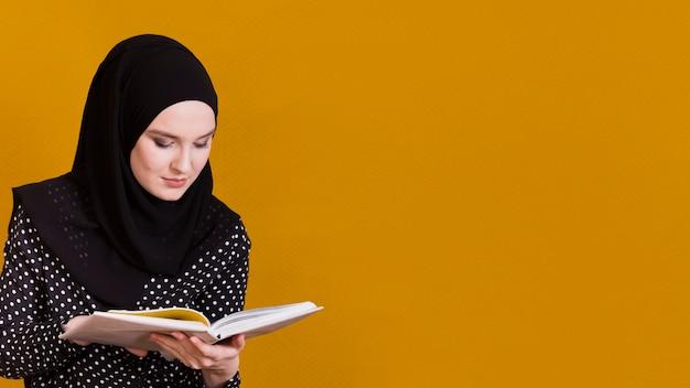 Mujer islámica con el libro de lectura del pañuelo delante del fondo con el espacio de la copia Foto gratis