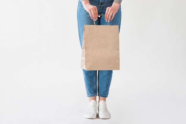 Mujer en jeans con bolsa de papel con víveres Foto gratis