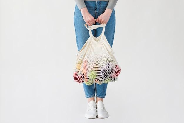 Mujer en jeans con bolsa reutilizable con comestibles Foto gratis