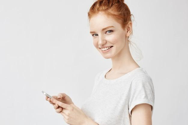 Mujer de jengibre sonriendo sosteniendo teléfono twitteando o usando las redes sociales en la pared blanca Foto gratis