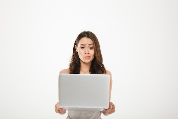 Mujer joven de 30 años mirando en la pantalla de su cuaderno plateado pensando o expresando malentendidos con cara, aislado sobre la pared blanca Foto gratis